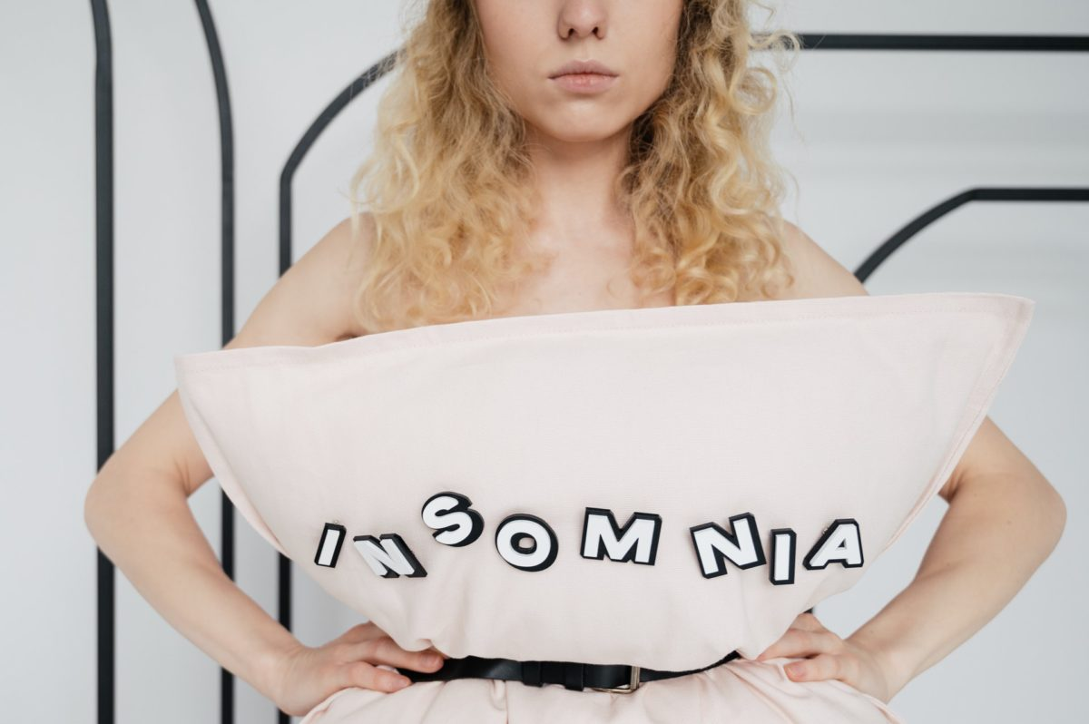 Woman with a sleep disorder in bed with a pillow that says insomnia