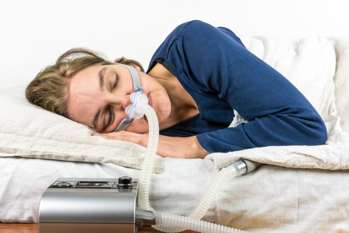 Woman using a CPAP machine to help with sleep apnea