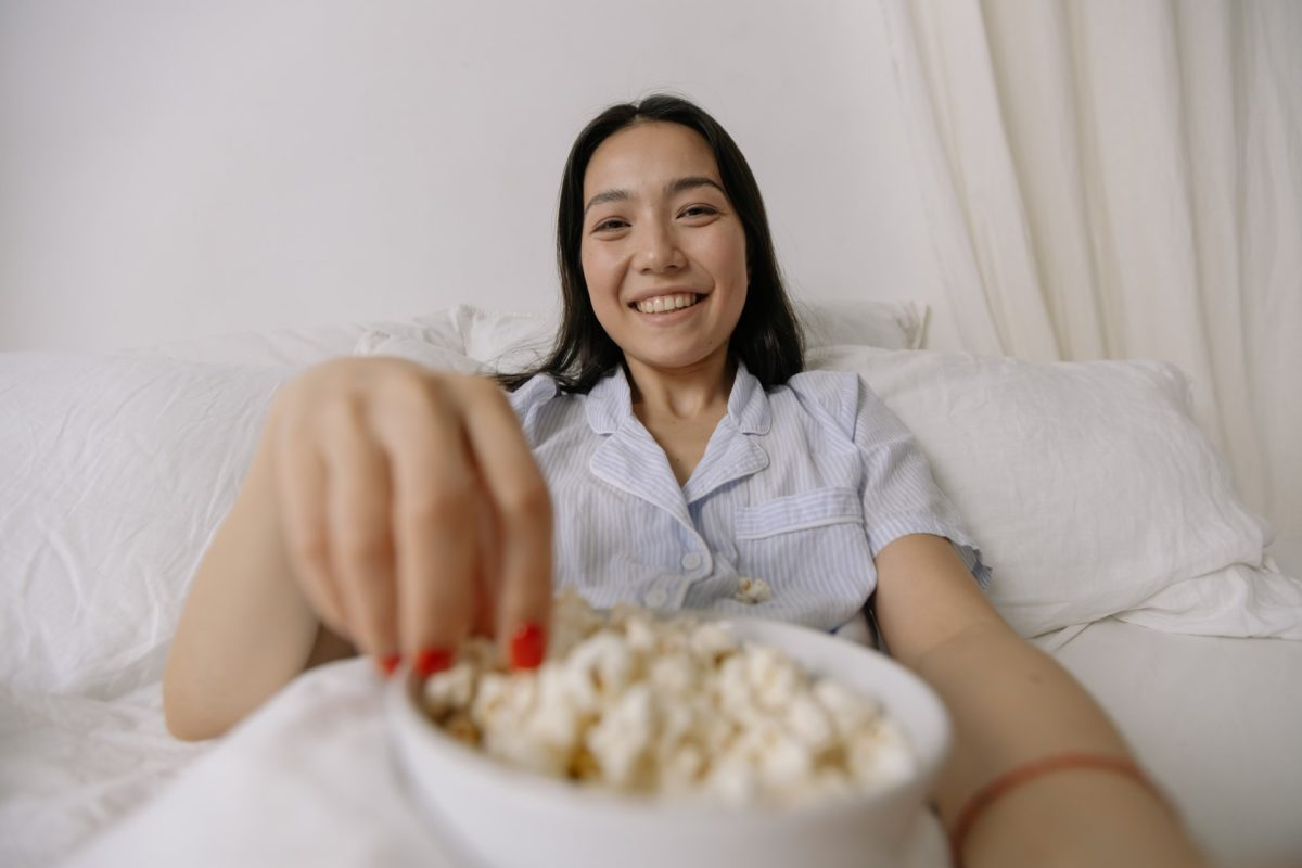 Young woman eating popcorn in bed before going to sleep