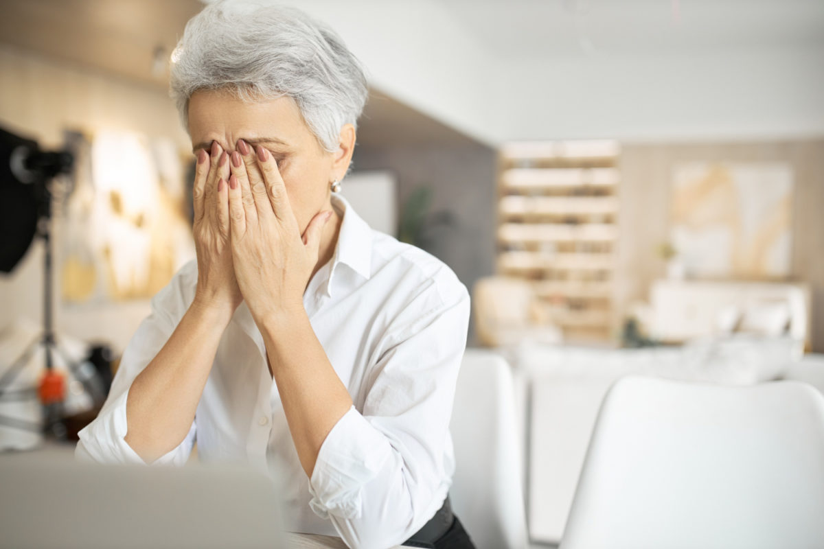 Senior woman who suffers from insomnia having trouble staying awake while working from home.